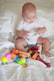 Happy little boy playing with toys in his bed Stock Photo