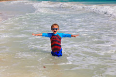 Happy little boy playing in waves at beach Stock Photography