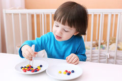 Happy little boy plays with pincers and beads. Educational playi Royalty Free Stock Image