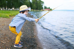 Happy little boy plays with stick on riverside Stock Photos