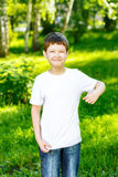 Happy little boy pointing his fingers on a blank t-shirt. Stock Photography