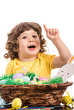 Happy little boy pointing up. Happy little boy two years age pointing up  to white space and sitting at table with Easter eggs Royalty Free Stock Image