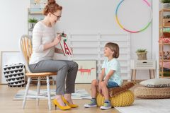 Boy during speech therapy session. Happy little boy with pronunciation and language difficulties during speech therapy session with young female doctor Stock Image