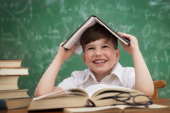 Happy little boy, pupil with book on head Royalty Free Stock Images