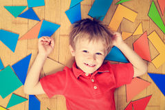 Happy little boy with puzzle toys on wooden floor Stock Image