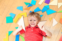 Happy little boy with puzzle toys on wooden floor Royalty Free Stock Images