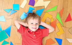 Happy little boy with puzzle toys on wooden floor Royalty Free Stock Photo
