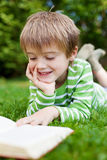 Happy little boy reading book in the garden Royalty Free Stock Photo