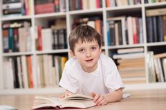Happy little boy reading a book at home. Stock Photos