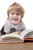 Happy little boy reading and smiling Royalty Free Stock Photo