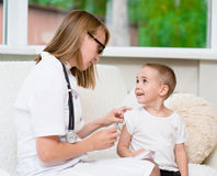 Happy little boy receiving injection or vaccine Stock Photo