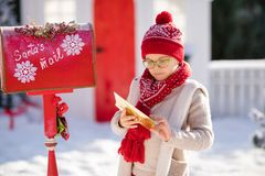 Happy little boy with red hat and green glasses sending her letter to Santa, Christmas time stock photos