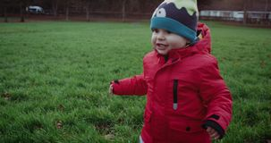 Happy little boy in red jacket running with smile in park. Child running on green grass. Slow motion 4k. stock video footage