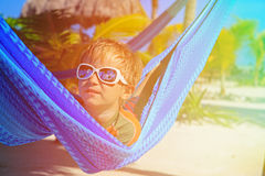 Happy little boy relaxed in hammock on the beach Royalty Free Stock Images