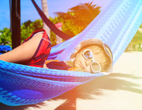 Happy little boy relaxed in hammock on the beach Stock Photos