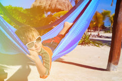 Happy little boy relaxed in hammock on the beach Stock Images