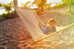 Happy little boy relaxed in hammock on the beach Stock Photo
