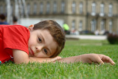 Happy little boy relaxing on the grass Stock Photo
