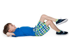 Happy little boy resting. A happy little boy is resting on the white background stock photography