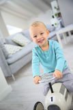 Happy little boy riding car toy at home Stock Image