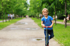 Happy little boy riding scooter in summer Royalty Free Stock Photo