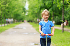 Happy little boy riding scooter in summer Stock Photography