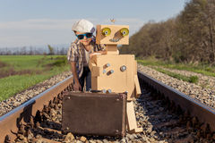 Happy little boy and robot walking with suitcase on the railway Royalty Free Stock Photography