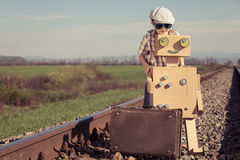 Happy little boy and robot walking with suitcase on the railway Royalty Free Stock Images