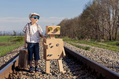 Happy little boy and robot walking with suitcase on the railway Royalty Free Stock Photo