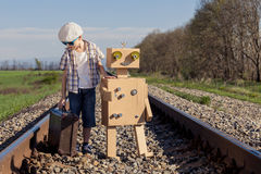 Happy little boy and robot walking with suitcase on the railway Stock Photos
