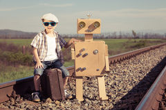 Happy little boy and robot walking with suitcase on the railway Stock Images