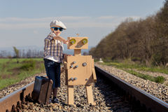 Happy little boy and robot walking with suitcase on the railway Stock Image