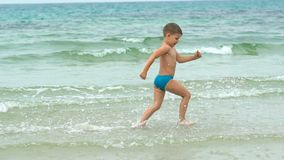 Happy little boy running along the sea shore at tropical beach.  stock footage