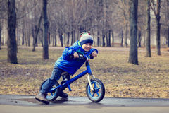 Happy little boy on running bike in spring Stock Photos