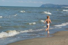 Happy little boy running far away along the sea beach Royalty Free Stock Image