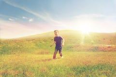 Happy little boy running on green field outdoors Stock Photo