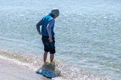 Happy little boy running and jumping in the waves on black Sea beach Stock Images
