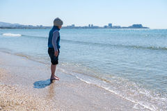 Happy little boy running and jumping in the waves on black Sea beach Stock Image