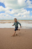 Happy little boy running at the sea coast Royalty Free Stock Photos
