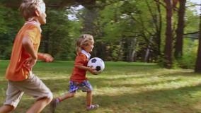 Happy little boy running with soccer ball stock footage
