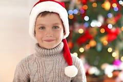 Happy little boy in Santa hat against blurred  Christmas tree. Happy little boy in Santa hat against blurred Christmas tree Royalty Free Stock Images