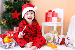Happy little boy in Santa hat with lollipop and presents. Sits near Christmas tree Stock Image