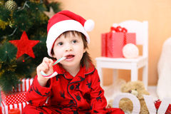 Happy little boy in Santa hat with lolly. Happy little boy in Santa hat with lollipop and presents sits near Christmas tree Stock Images