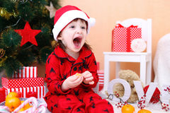 Happy little boy in Santa hat. Lovely little boy in Santa hat with tangerine sits near Christmas tree Royalty Free Stock Images