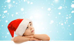 Happy little boy in Santa hat peeking from behind. Blank sign billboard. Space for Your Text. Sale, holidays, christmas, new year, x-mas concept Royalty Free Stock Images