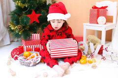 Happy little boy in Santa hat with present Stock Photography