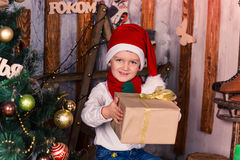 Happy little boy in Santa's costume with the present near Xmas tree Royalty Free Stock Photography