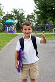 Happy little boy with school backpack and book in the play yard Royalty Free Stock Photos