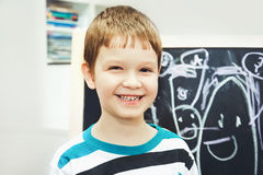 Happy little boy before the school board with the alphabet. Educ Royalty Free Stock Photography