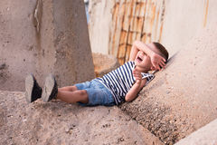Happy little boy in singlet and shorts lies on a concrete breakwater closing his eyes with hand. Laughing little boy in a vest and shorts lies on a concrete Stock Photos